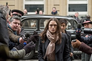 Keira Knightley walks out of her car as reporters point microphones at her