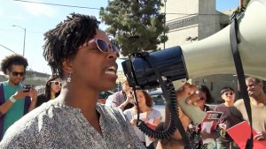 A woman talking into a megaphone as several people look on behind her