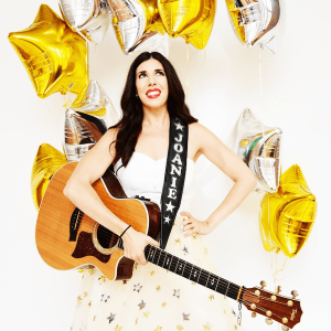 Joanie Leeds holding a guitar with the strap saying Joanie on it in front of yellow star balloons