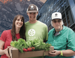 Three stars of Hearts of Glass smiling together in front of mountains and a greenhouse holding plants.