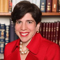 Rabbi Julie Schonfeld in front of a bookcase, smiling