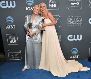 Glenn Close and Lady Gaga holding their Critics' Choice Awards, smiling in front of a banner with logos for the awards, AT&T and the CW.