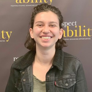 Charlotte Ruda smiling in front of the RespectAbility banner