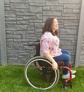 Cami Howe facing to the right, laughing, looking at something off camera. Cami is a wheelchair user