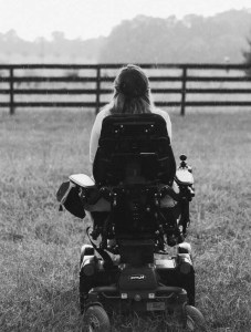 Ariella Barker (from behind) looking at a forest outside. Ariella is using a wheelchair