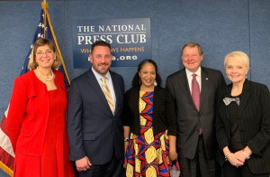 L-R: Jennifer Laszlo Mizrahi, Aaron Dorfman, Kerrien Suarez, Steve Bartlett and Stephanie Powers smiling in front of a sign for the National Press Club (Where News Happens Press.org), an American flag, and a blue wall