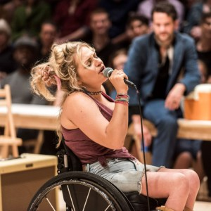 Ali Stroker singing into a microphone on stage for Oklahoma!