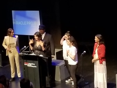 Robia Rashid speaking at a podium surrounded by cast members of Atypical