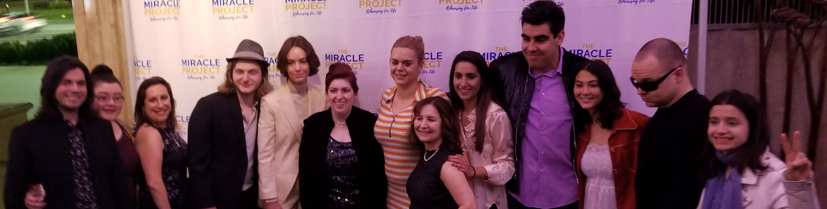 A group of cast members with Elaine Hall posing for a picture in front of a banner saying The Miracle Project