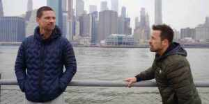 Warren Christie and Kurt Yaeger talking on The Village in front of the Hudson River with New York City's skyline in the background