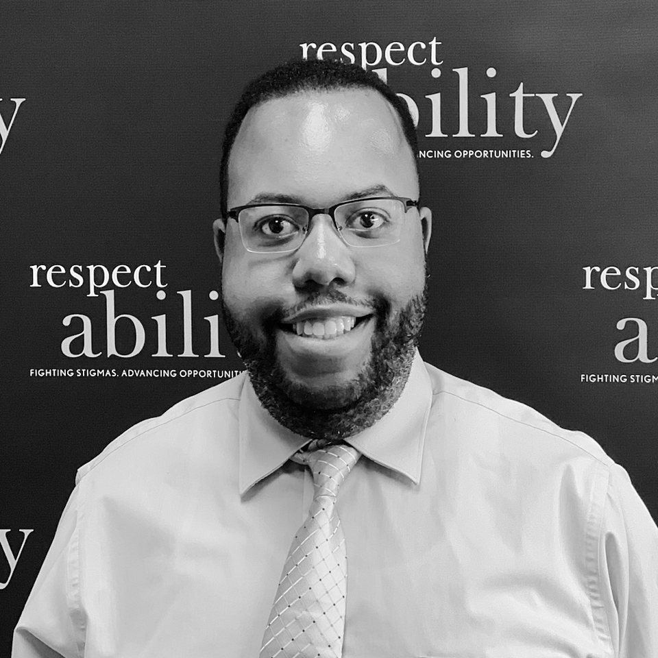 Anthony Rendolph Clarke Brown II smiling in front of the RespectAbility banner