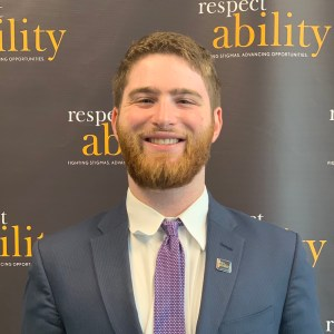 Adam Fishbein smiling in front of the RespectAbility banner