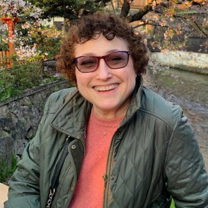 Ila Eckhoff smiling outside in front of trees and plants wearing glasses
