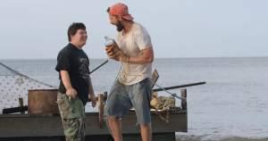 "Zak (Zack Gottsagen), left, and Tyler (Shia LaBeouf), right, near a raft they built in ""The Peanut Butter Falcon"""