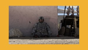 Still from Fort Irwin with Cristian Valle in a military uniform sitting outside leaning against a wall. Christian is a double amputee, and has no legs.