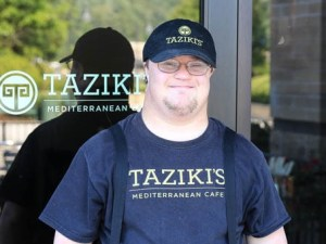 A worker with a disability standing outside Taziki's Mediterranean Cafe wearing a hat and shirt with the restaurant's logo on it