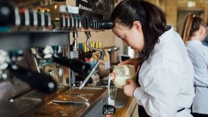 A woman with a disability making coffee at 321 Coffee.
