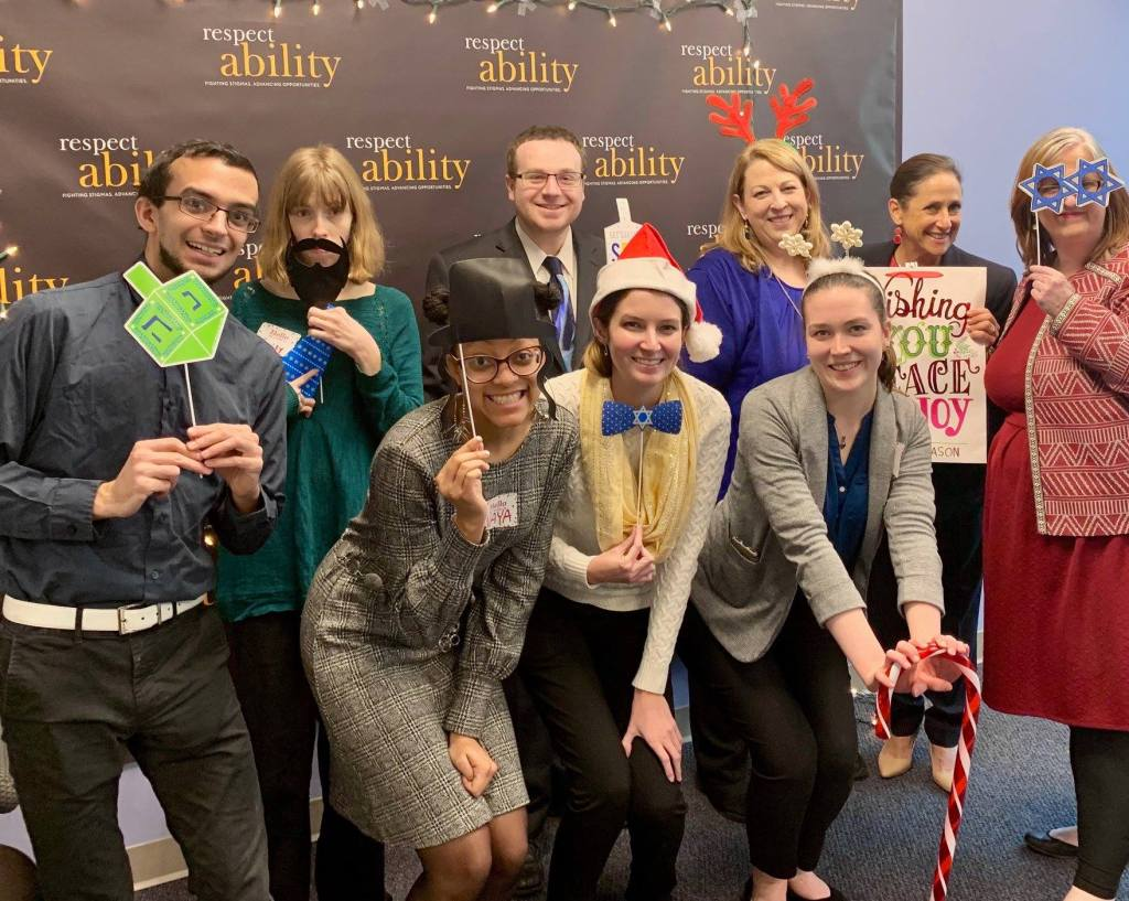 RespectAbility Fall 2018 Fellows with Debbie Fink wearing holiday-related accessories in front of the RespectAbility banner
