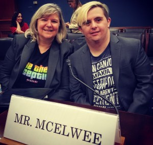 Sandra and Sean McElwee smile together in a Capitol Hill hearing room behind a sign that says Mr. McElwee