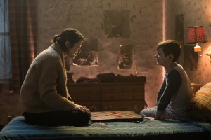 A scene from The Parts You Lose with a woman talking to a young boy sitting on a bed. The young boy has a cochlear implant.