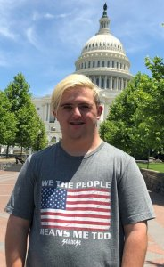 Sean McElwee wearing a shirt that says We The People Means Me Too with an American flag and the Seanese logo on it, standing in front of the Capitol dome.