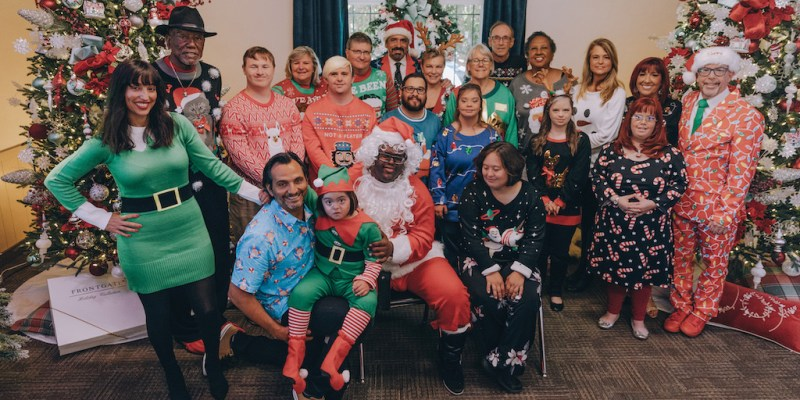 The cast of Born This Way, including their families, smiling together in front of Christmas trees wearing festive clothes