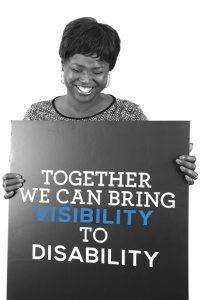 "A woman holding a sign that says ""Together we can bring Visibility to Disability"", smiling"