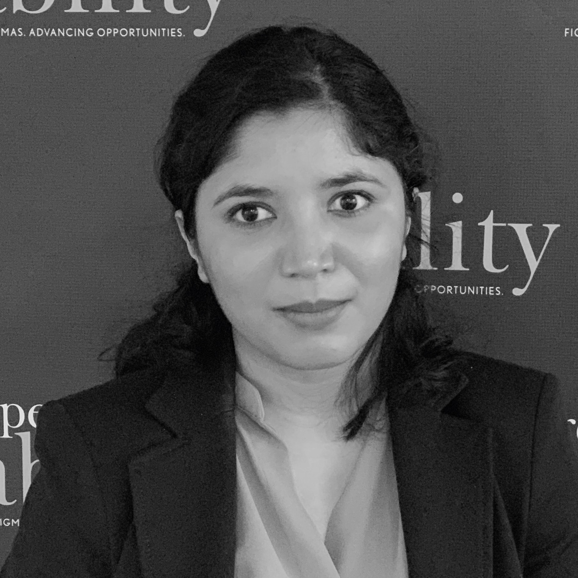 Baksha Ali smiling in front of the RespectAbility banner