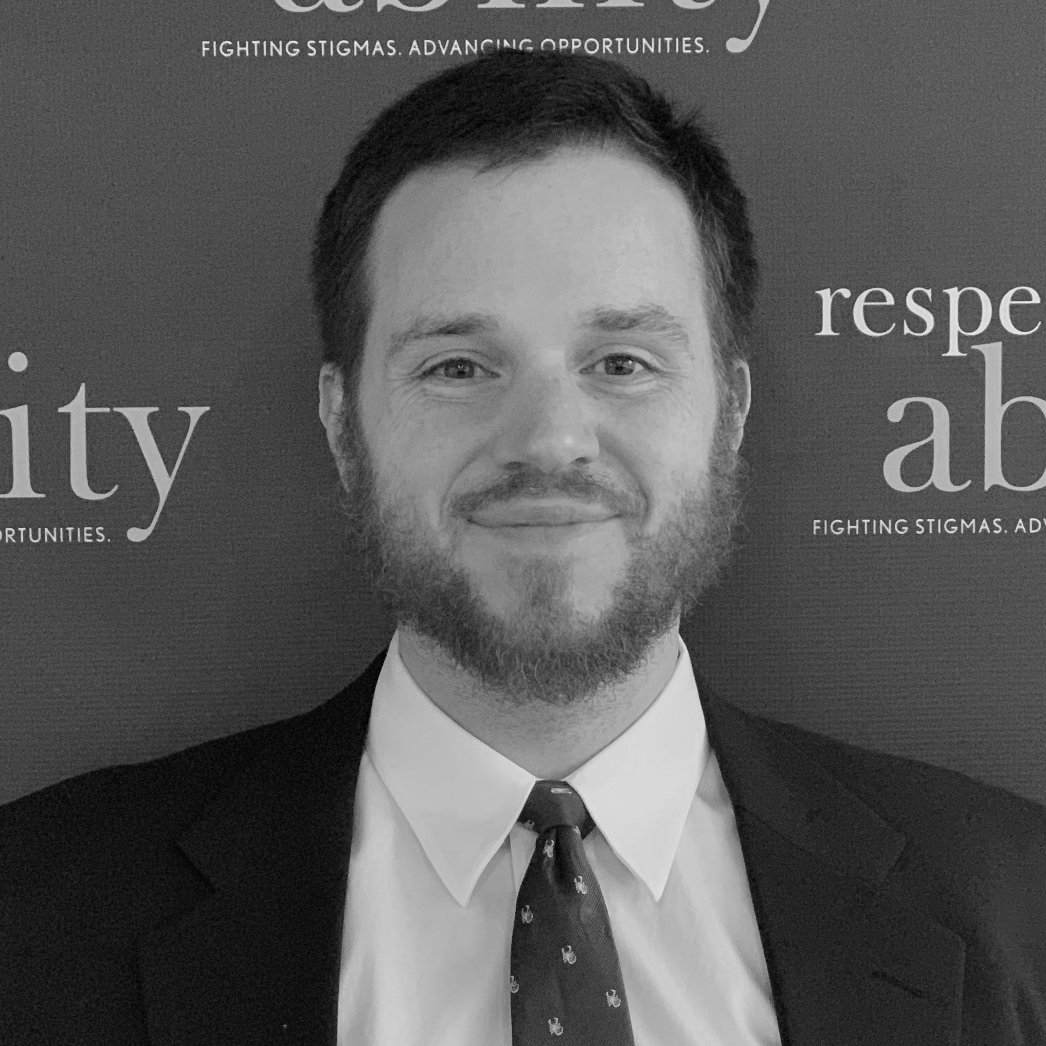 Geoff Hoppe smiling in front of the RespectAbility banner