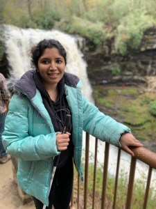 Baksha Ali smiling holding a white cane holding onto a railing next to a river with a waterfall behind her