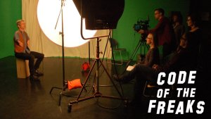 A person with a disability being interviewed for the documentary Code of the Freaks. Logo for the film in bottom right