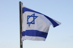An Israeli flag flying against a blue sky.