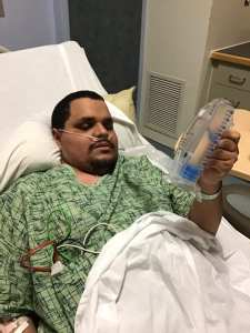 Leo Cantos lying in a hospital bed holding a tool for breathing exercises