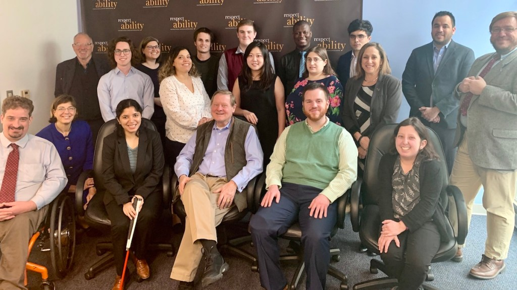 Steve Bartlett with RespectAbility Staff and Spring 2020 Fellows smiling in front of the RespectAbility banner