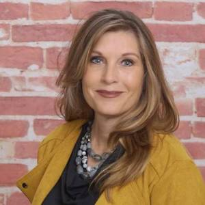 Carla Boyd smiling headshot in front of a brick wall