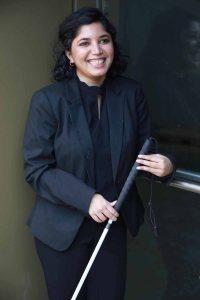 Baksha Ali holding a white cane, smiling