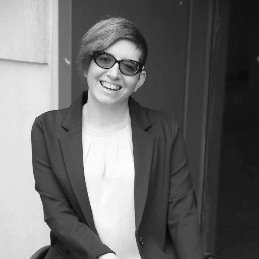Lauren Arena smiling wearing glasses and a suit jacket.