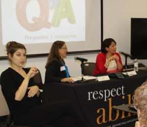 Debbie Fink smiles seated next to Carol Robles-Roman at a panel for Latinas with disabilities. Q&A sign behind them, ASL interpreter to the left.
