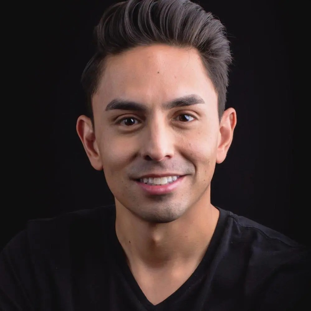 Danny Gomez smiling headshot wearing a black shirt in front of a black backdrop