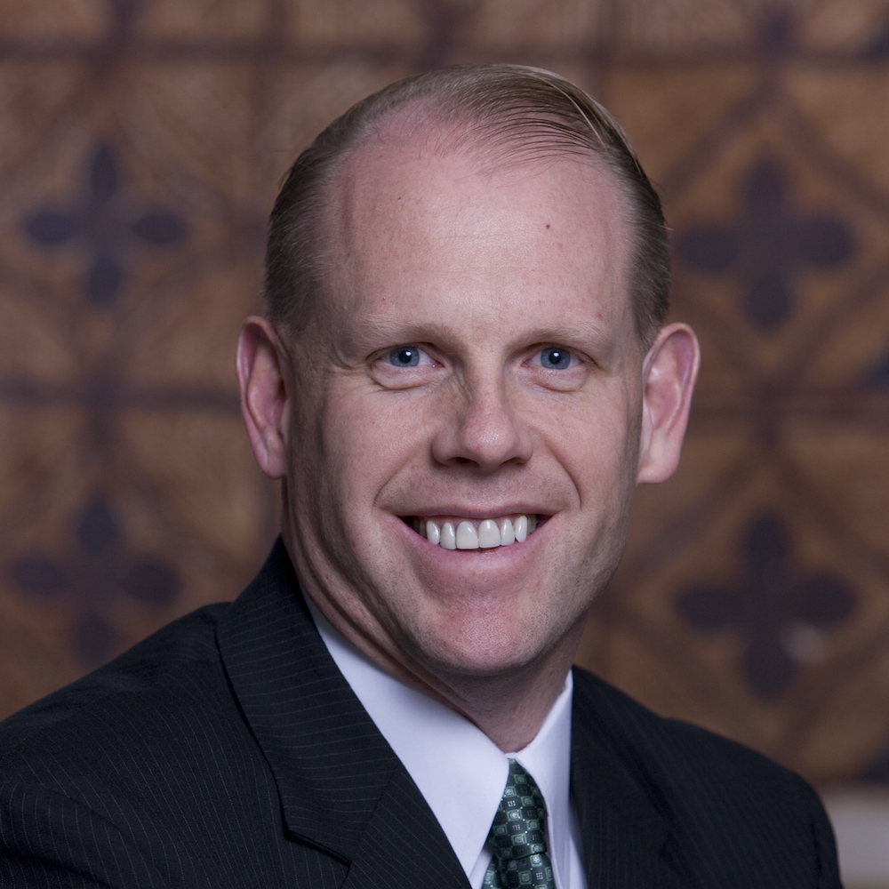Mark Feinour smiling wearing a suit and tie. Mark is a white man with short brown hair.