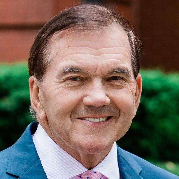 Governor Tom Ridge headshot wearing a blue suit and pink tie. Ridge is a white man who has short brown hair