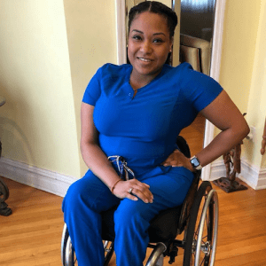 Andrea Dalzell wearing scrubs, smiling. Dalzell is a person of color who uses a wheelchair