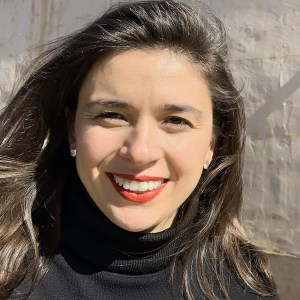 Alexandra Grossi headshot smiling in front of a wall