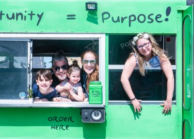 the Chernotsky family looking out the windows in a green bus, smiling
