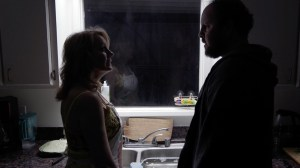 Eileen Grubba and Austin Basis talking with each other in a dark kitchen in a scene from Dead End Drive