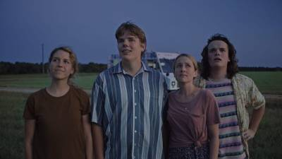 Still from Drought with the four stars looking at something in an empty field