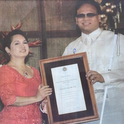 Ollie Cantos, dressed in Barong Tagalog, formal Filipino attire worn only on special occasions, accepting the Pride of the Filipino Award as presented by now-former Philippine President Gloria Macapagal-Arroyo at Malacañan Palace. Ollie's Baromg is white with fabric made from pineapple fibers. President Arroyo is wearing a red dress.