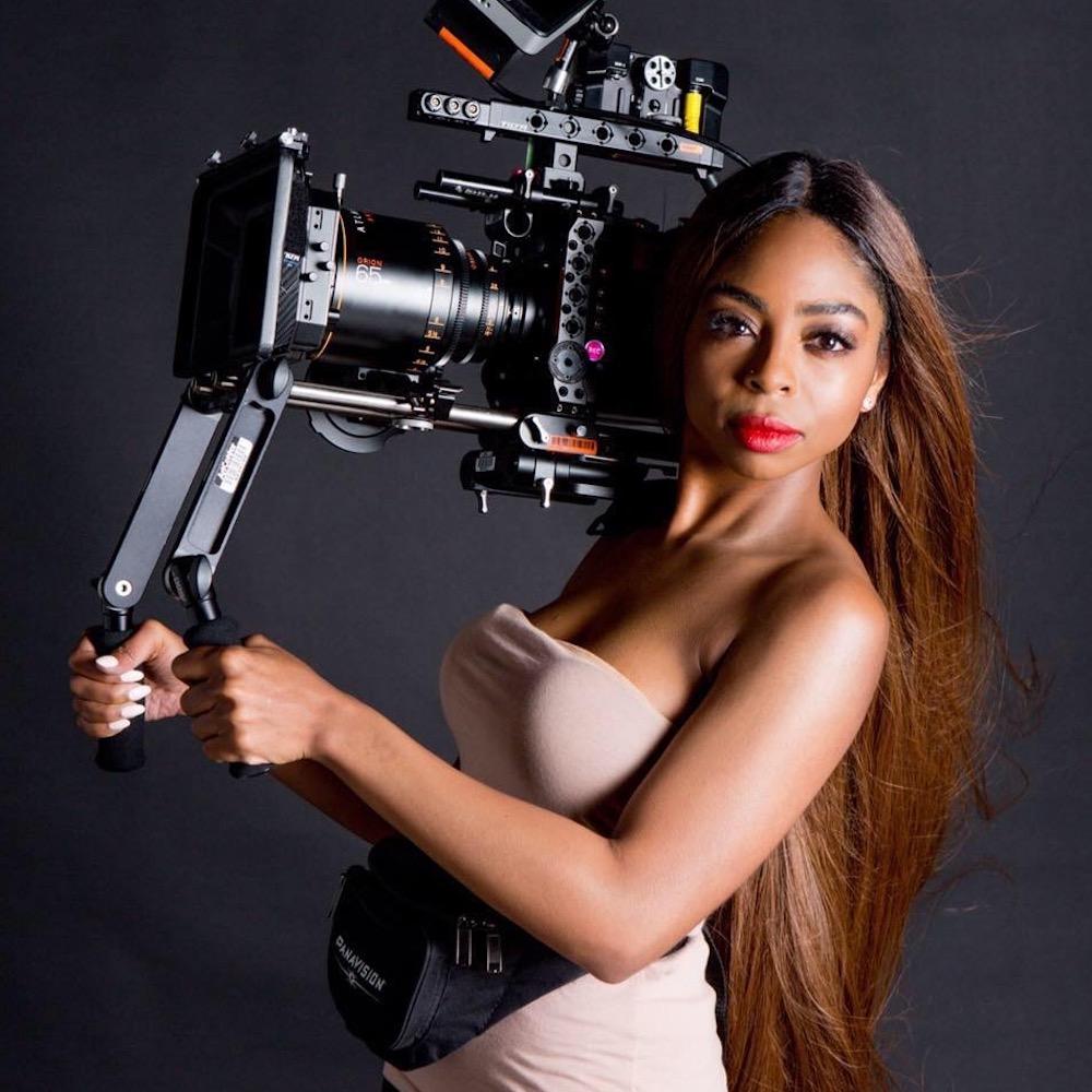 Kimisha Renee Davis headshot holding a large camera.