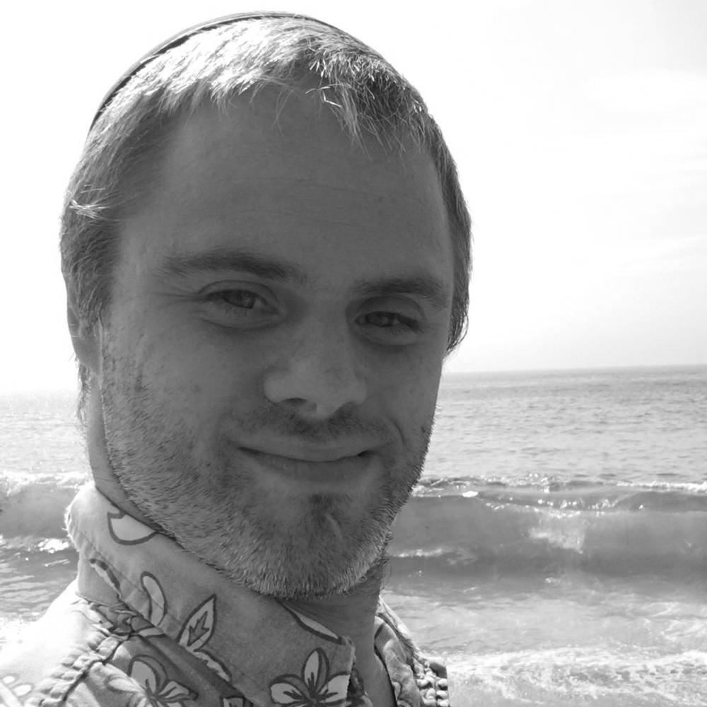 Shlomo Meyers smiling headshot on the beach with the ocean behind him