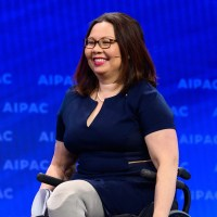 Tammy Duckworth on stage smiling with the AIPAC logo behind her.